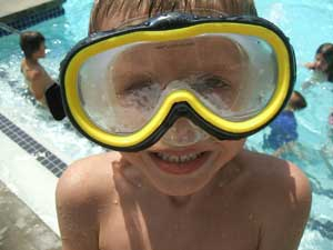 Boy wearing large face mask goggles and smiling, beside a swimming pool where children play in the w